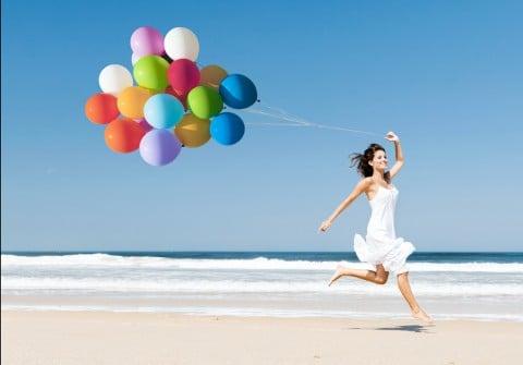 女性 元気 風船 海 砂浜