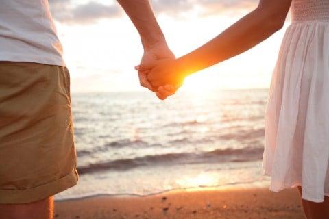 カップル 夫婦 愛情 手をつなぐ 海辺 夕日 恋愛