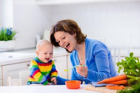 笑顔で離乳食を食べさせるママ
